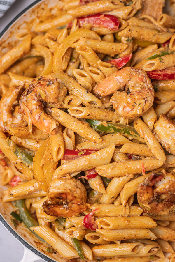 a close shot of a colourful creamy pasta with shrimps and bell peppers.